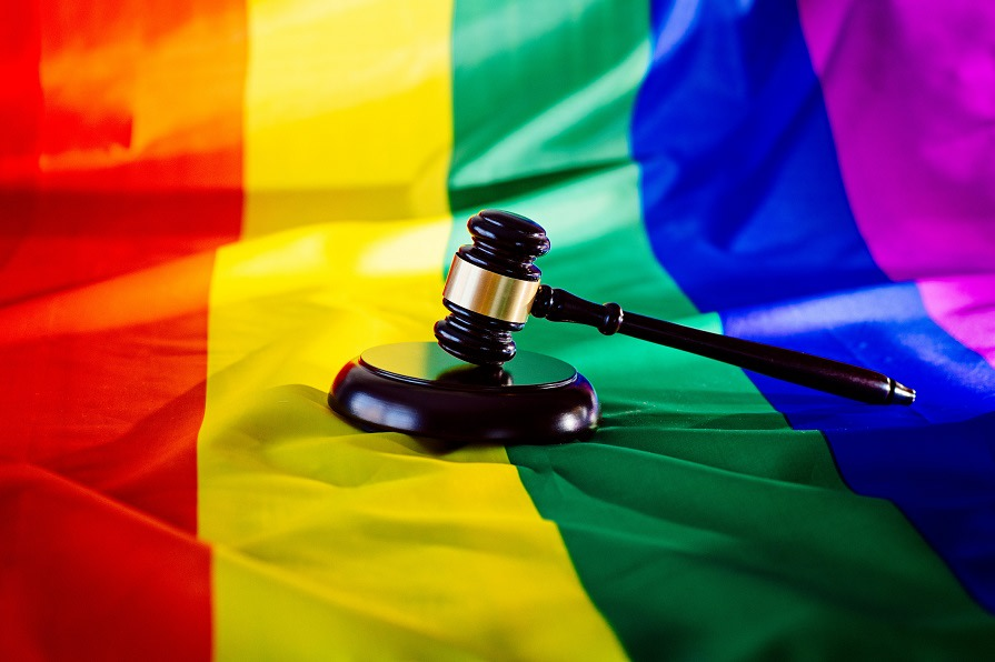 Woden judge mallet symbol of law and justice with lgbt flag in rainbow colours. Lgbt rights and law