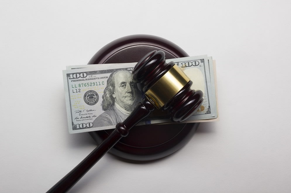 judge gavel on american dollars on white background.
