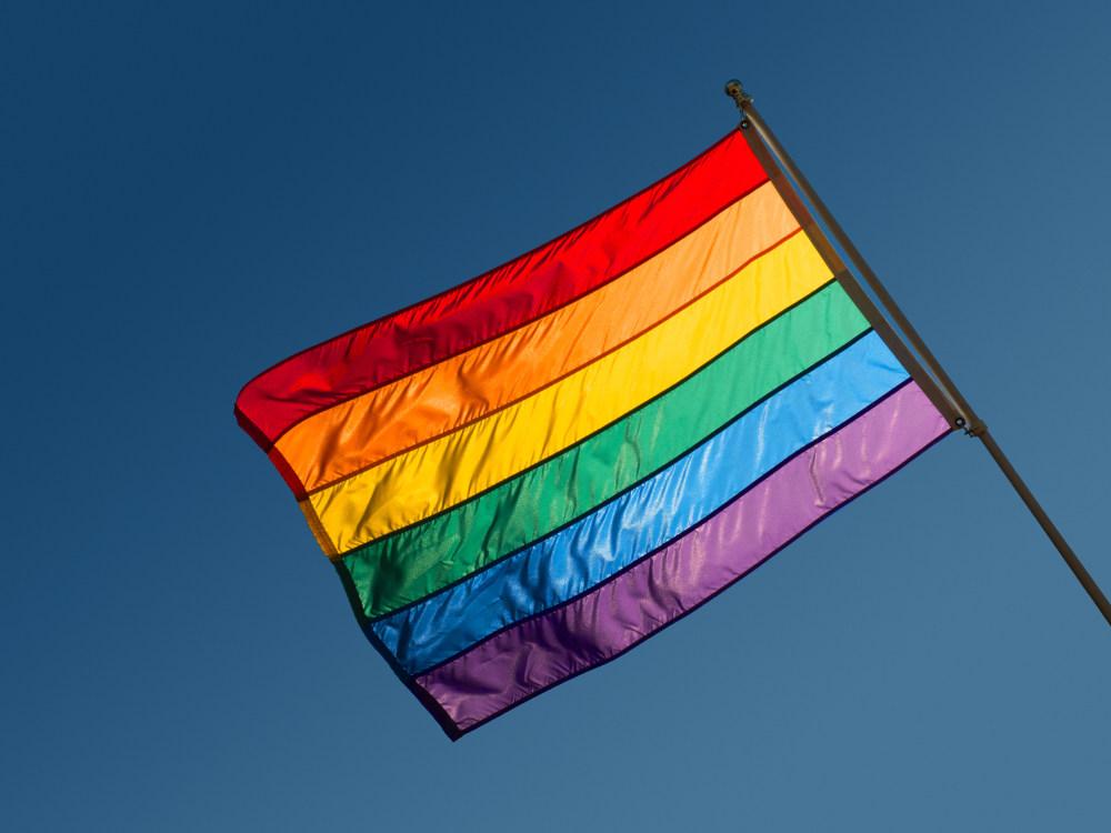 Photograph of a rainbow flag against a clear blue sky.