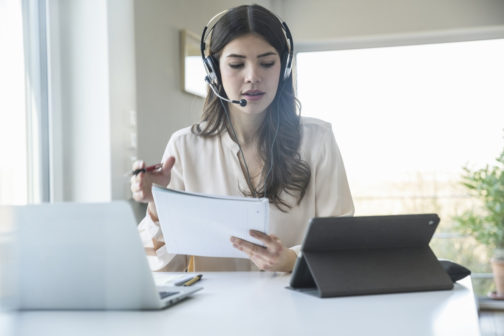 Woman works remotely with a headset, laptop, tablet, and a stack of papers