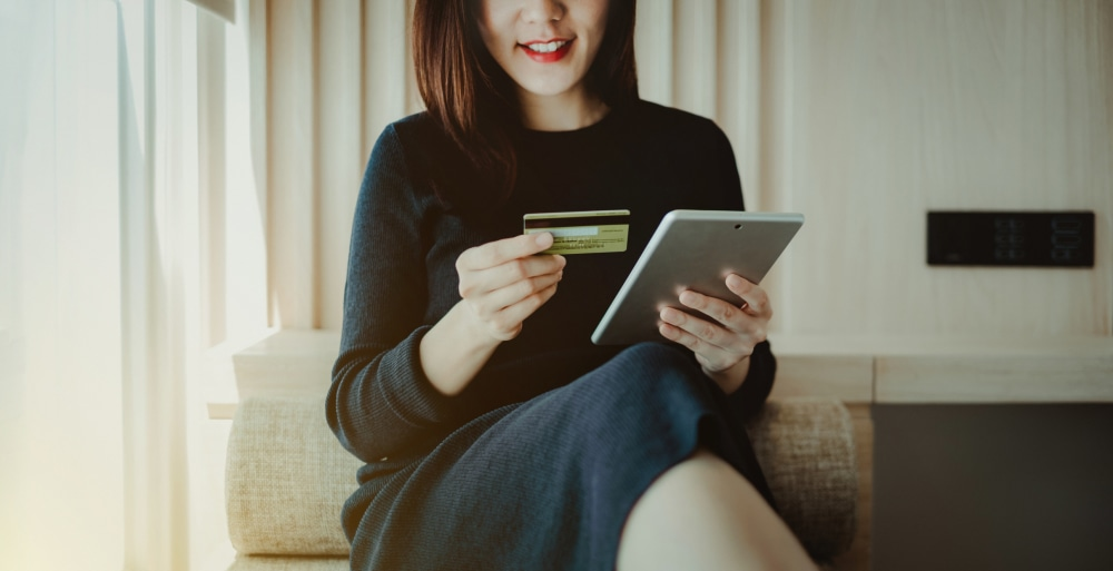 Young woman shopping online with credit card and digital tablet