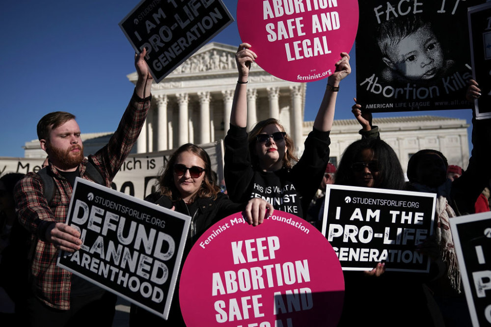 WASHINGTON, DC - JANUARY 19:  Pro-life activists try to block the signs of pro-choice activists in front of the the U.S. Supreme Court during the 2018 March for Life January 19, 2018 in Washington, DC. Activists gathered in the nation's capital for the annual event to mark the anniversary of the Supreme Court Roe v. Wade ruling that legalized abortion in 1973.  (Photo by Alex Wong/Getty Images)