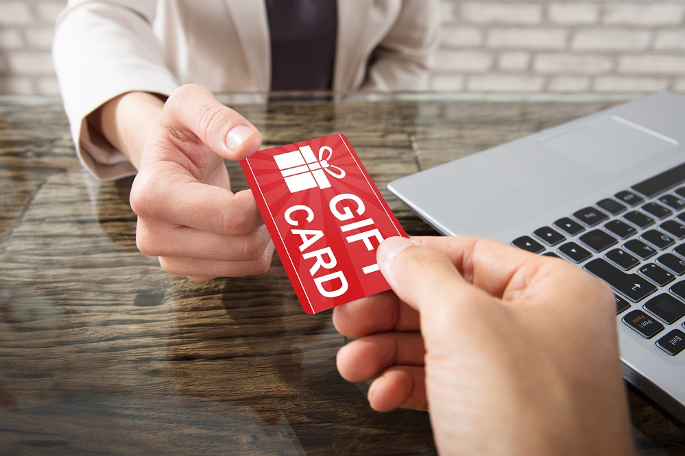 Close-up Of Two Hands Holding Gift Card