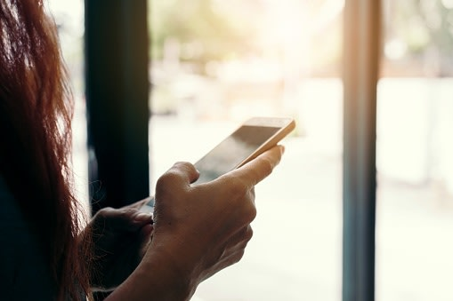 Young business woman paying with credit card on smart phone at home office