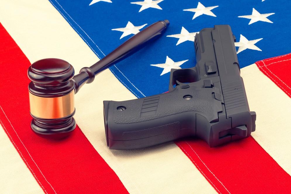 Judge gavel and gun over american flag - studio shot. Filtered image: cross processed vintage effect.