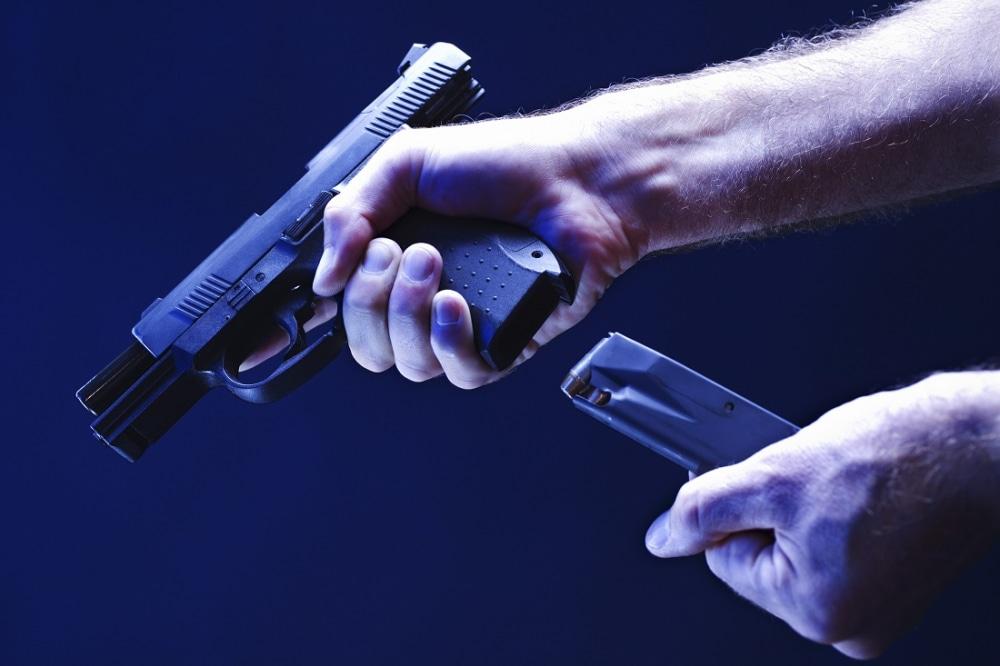 Hands loading magazine into handgun