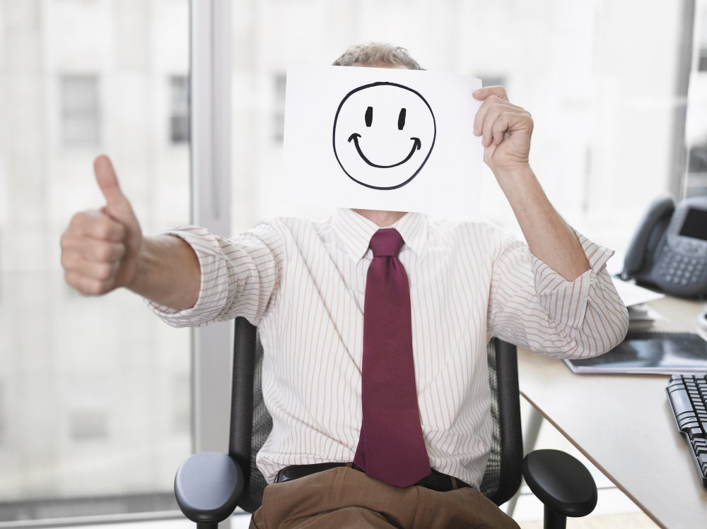 Man at desk holding up a smiley-face paper