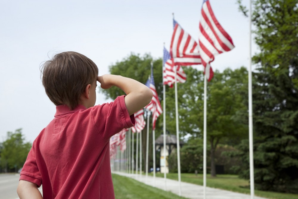 Young boy salutes flags of Memorial Day display in a small townOther images: