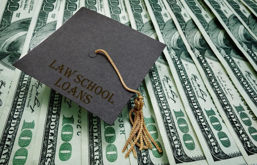 Law school graduation hat on assorted hundred dollar bills