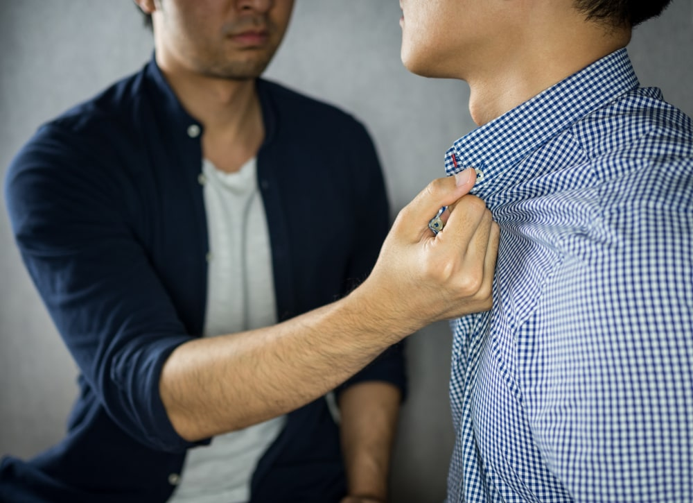 one man, from the mouth down, grabbing the shirt collar of another man, also from the neck down