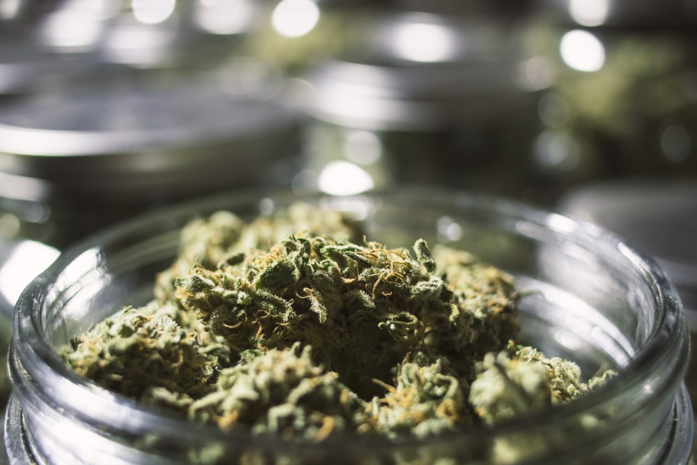 Overflowing marijuana buds in glass jar close up with a blurry background