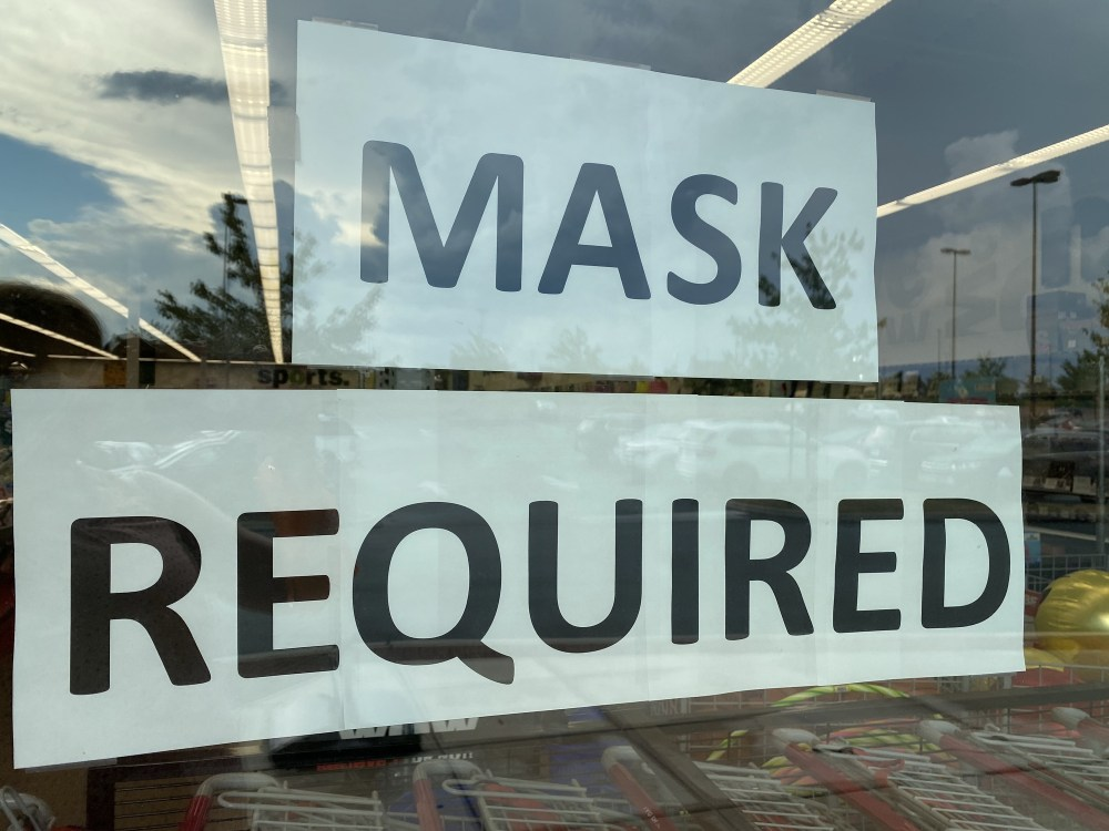 A store displays a sign in its window that reads mask required during the COVID-19 pandemic