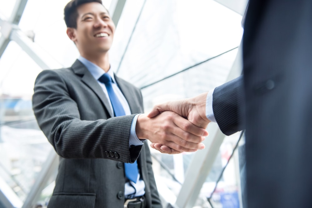 Young businessman leader making handshake with partner - greeting, dealing, merger and acquisition concepts