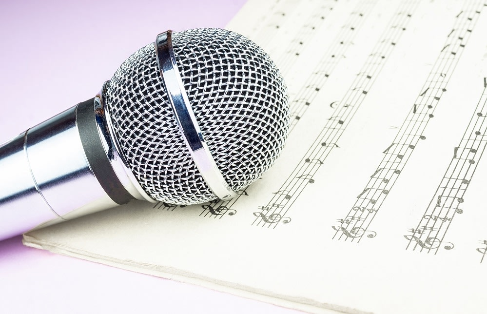 The musical microphone lies on a clean sheet music. Music concert. The singer and the song