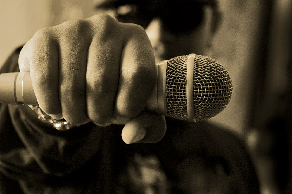 Musicians gripping a microphone in hand.