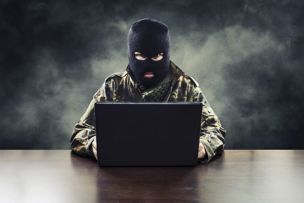 Masked cyber terrorist in military uniform hacking army intelligence