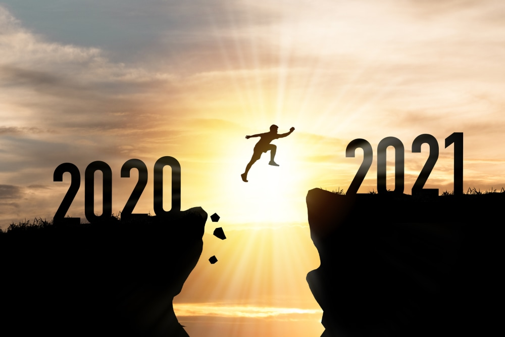 Welcome merry Christmas and happy new year in 2021,Silhouette Man jumping from 2020 cliff to 2021 cliff with cloud sky and sunlight.