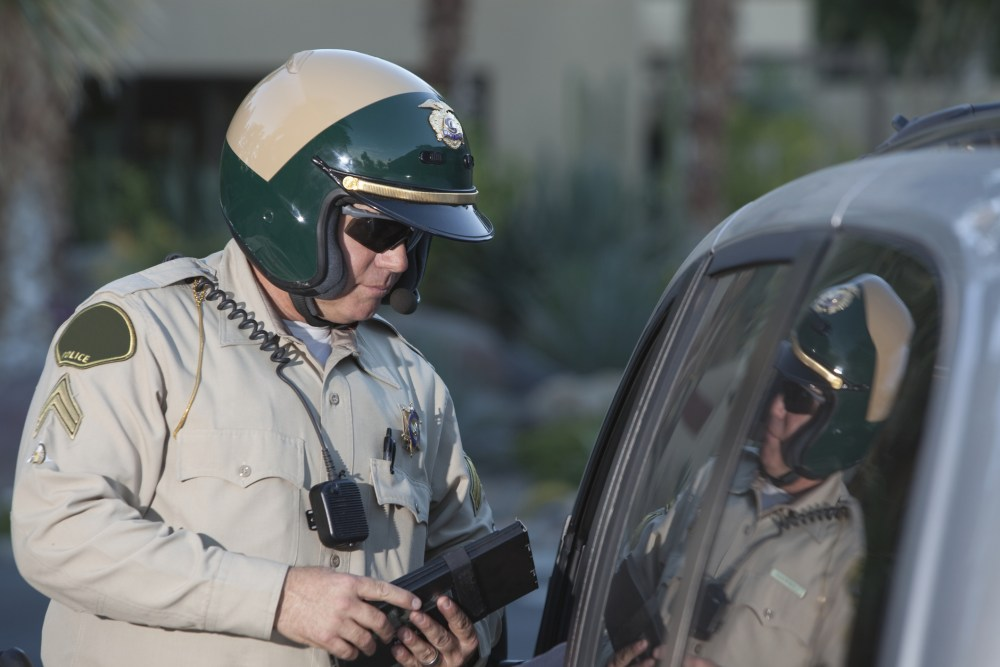 Patrol officer stands at window of luxury car