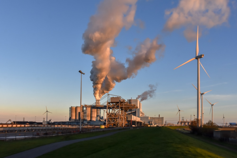A coal powerplant and windturbines side by side in the Eemshaven in the North of Holland