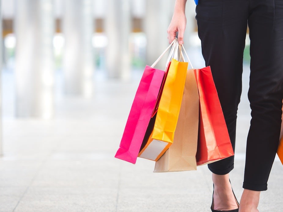 Close up woman holding shopping bag with colorful walking in the city with copyspace