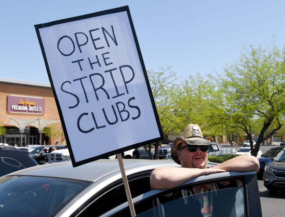 LAS VEGAS, NEVADA - APRIL 24:  Strip club DJ Jack Slammy of Nevada displays a sign as people gather for a protest caravan along the Las Vegas Strip hosted by conservative radio talk show host Wayne Allyn Root to demand the reopening of the Nevada economy, hit hard by coronavirus-related closures, on April 24, 2020 in Las Vegas, Nevada. Root broadcast his show from his car during the protest, which comes after Las Vegas Mayor Carolyn Goodman made controversial comments arguing against Nevada Gov. Steve Sisolak's stay-at-home order and closure of nonessential businesses to help combat the spread of the coronavirus. Sisolak said there needs to be a 14-day decline in COVID-19 cases and hospitalizations along with expanded testing and tracing capacity before the state can enter phase one of reopening.  (Photo by Ethan Miller/Getty Images)