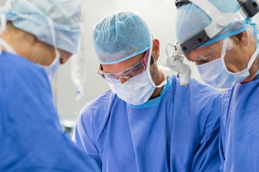 Team of focused surgeon at work on operation in hospital. Medical team performing operation. Mature surgery staff in the operating room working on patient.