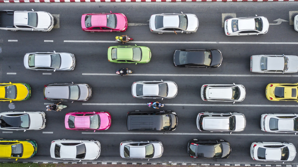 Aerial drone photograph of traffic jam in metropolis city with lots of cars qued on lanes.