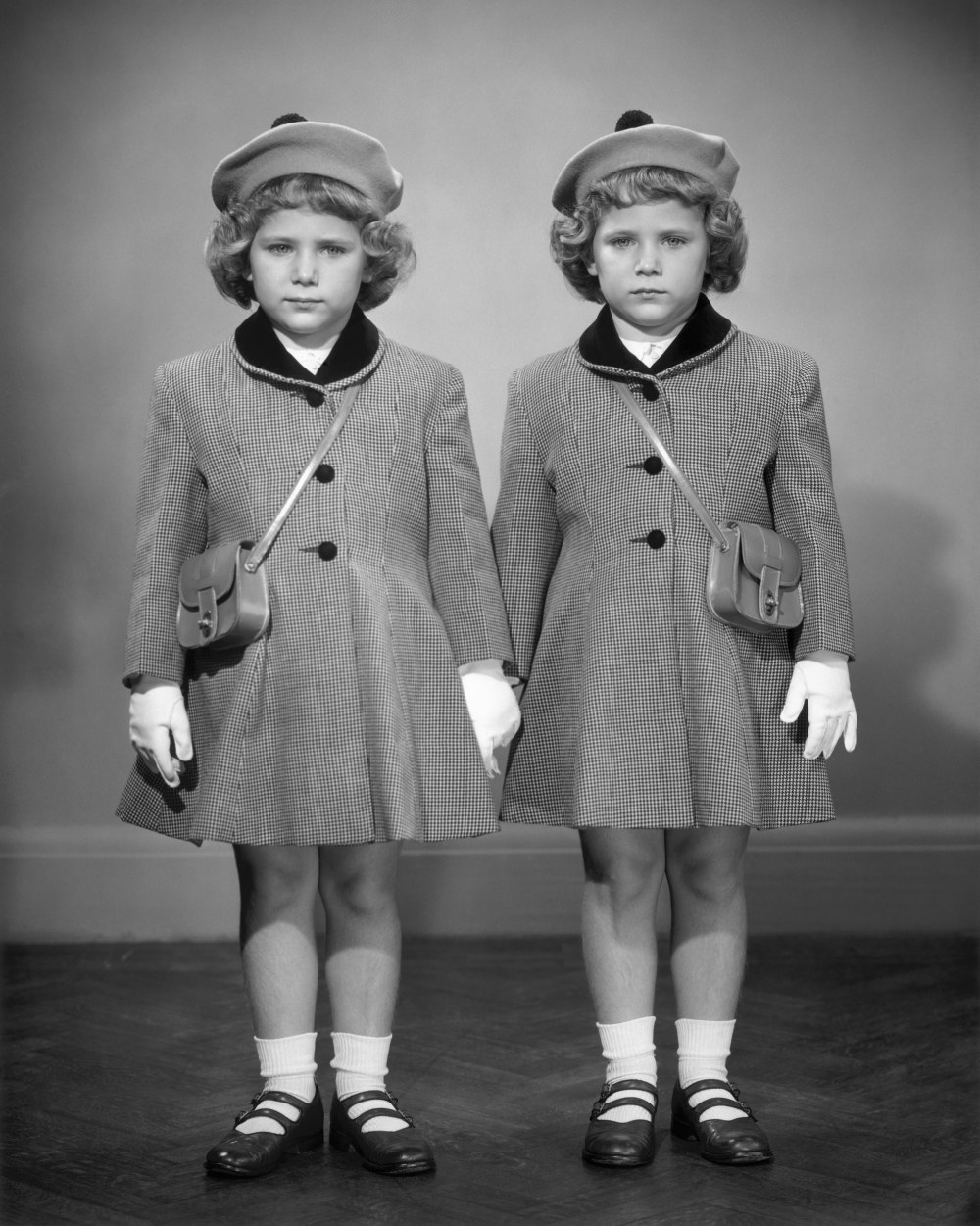 UNITED STATES - CIRCA 1950s:  Twin girls in hats & coats wearing white gloves.