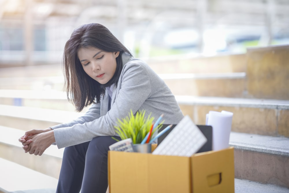 Woman who has lost her job, sitting on steps