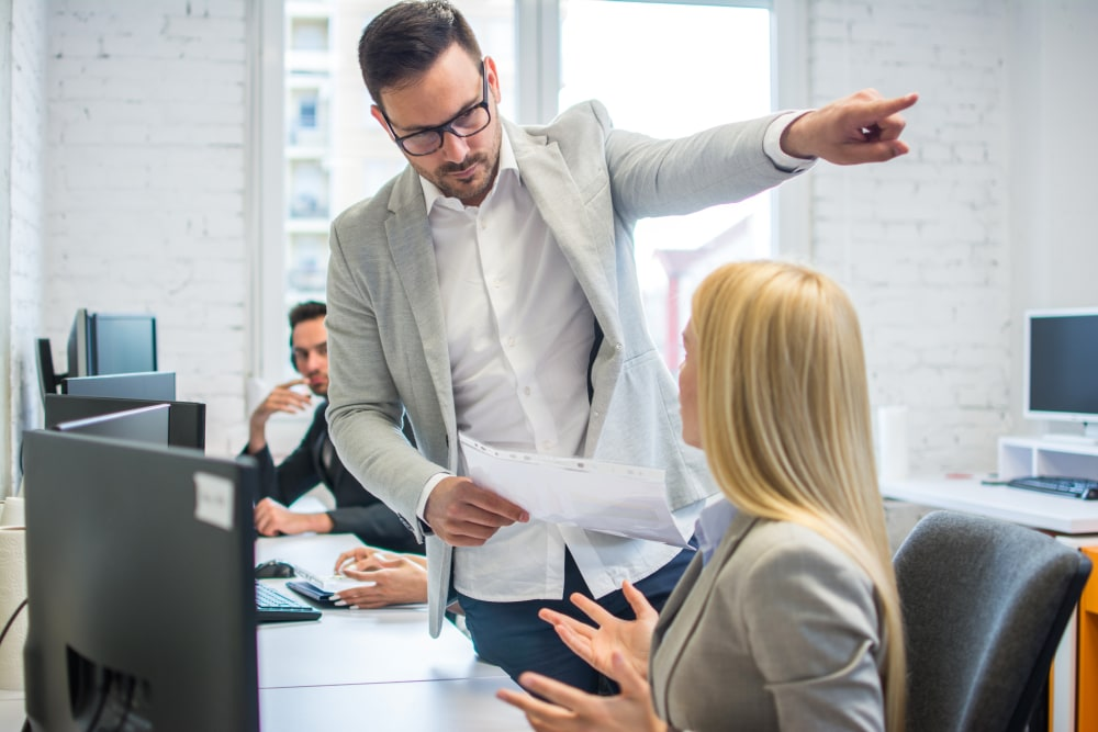 Male boss pointing at female employee to leave
