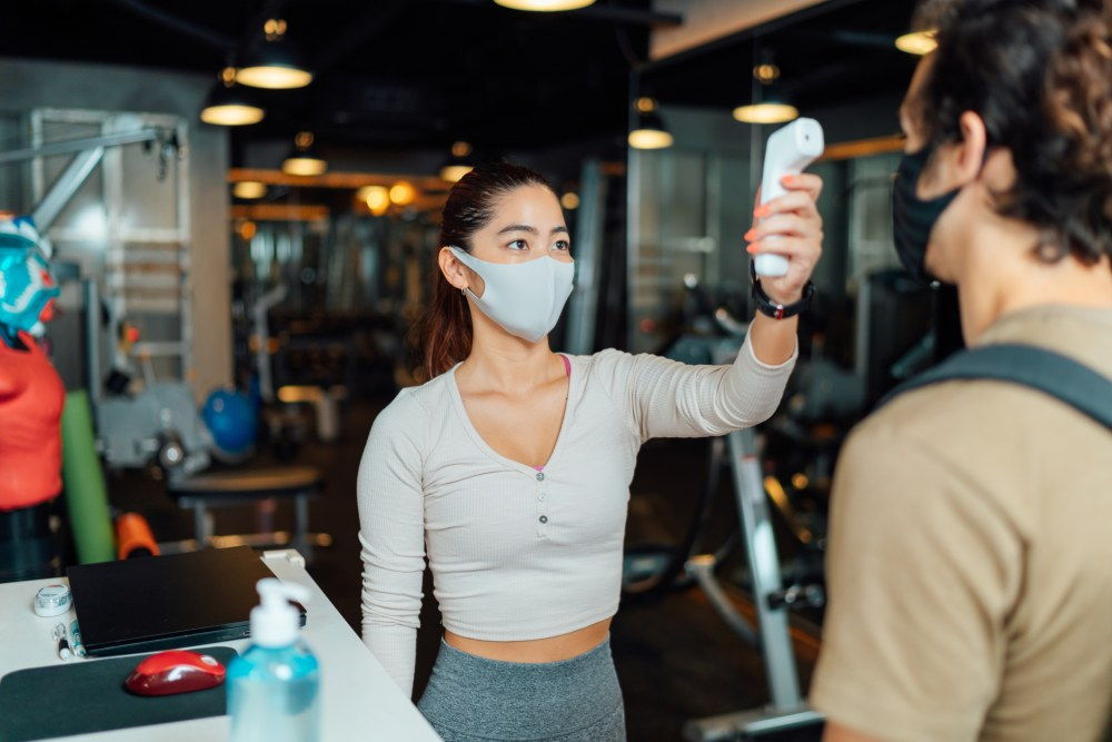 A female gym owner is using an infrared thermometer to check customer's body temperature at the entrance of the gym.