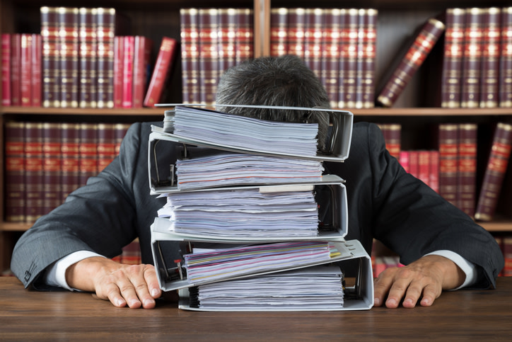 Frustrated businessman with lot of files on desk against gray background