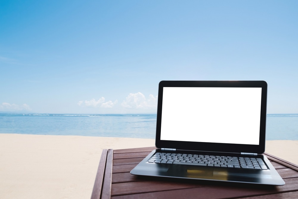 Laptop computer on wood table at the beach in summer