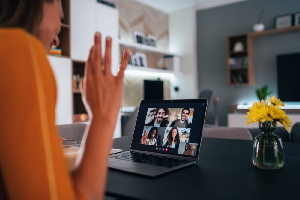 Woman using laptop for video conference to connect with her family, colleagues and friends from home