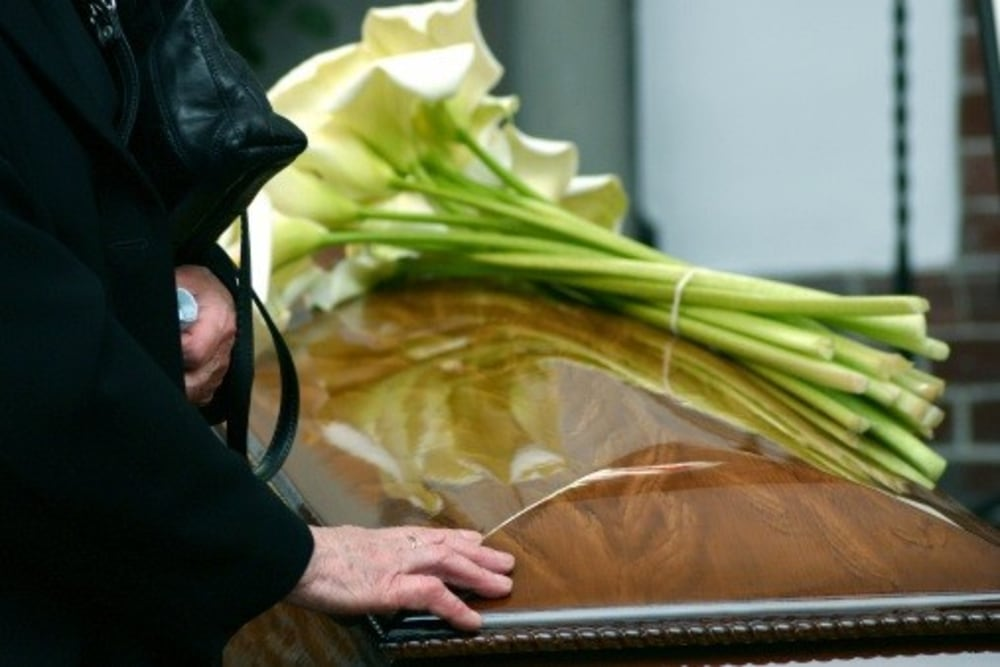 a hand placed on a coffin during a funeral